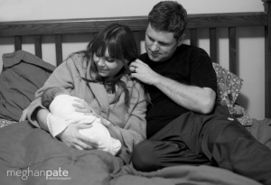 A new family snuggles in their own bed just after birth.